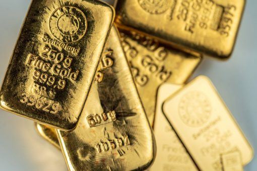 Several cast and minted gold bars on a on grey background. Selective focus.